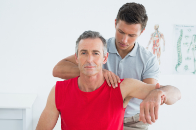 caregiver giving physical therapy to a senior man
