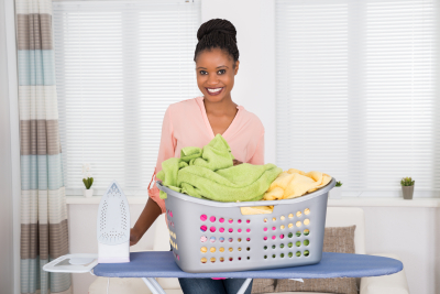smiling young woman with iron and basket full of clothes