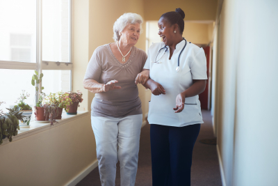 portrait of happy healthcare worker walking and talking with senior woman