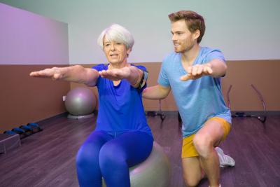 gym instructor assisting senior woman